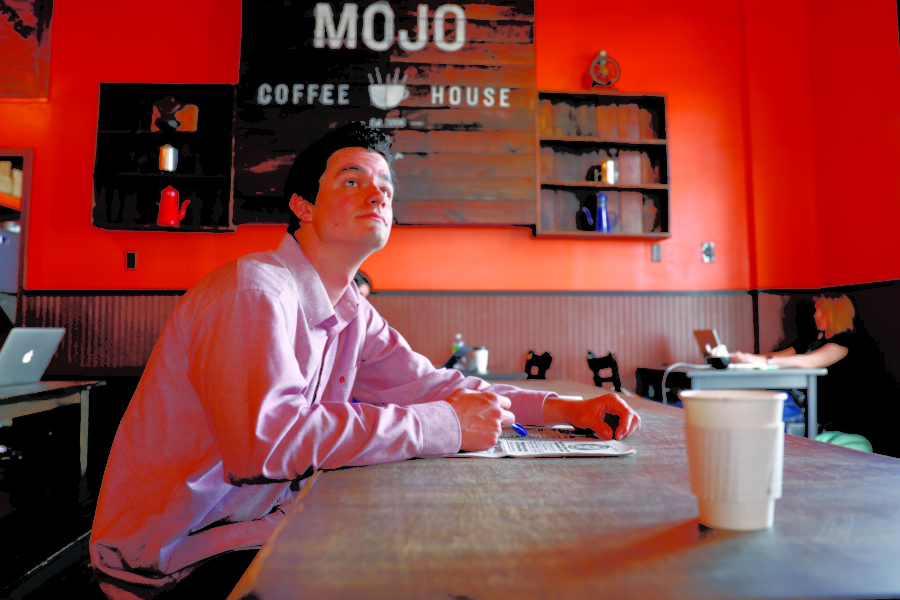 Caleb+Beck+sits+inside+Mojo+Coffee+House.+He+is+one+of+many+who+come+to+enjoy+the+establishment%E2%80%99s+food+and+drinks+as+well+as+calm+working+environment.+Photo+credit%3A+Barbara+Brown