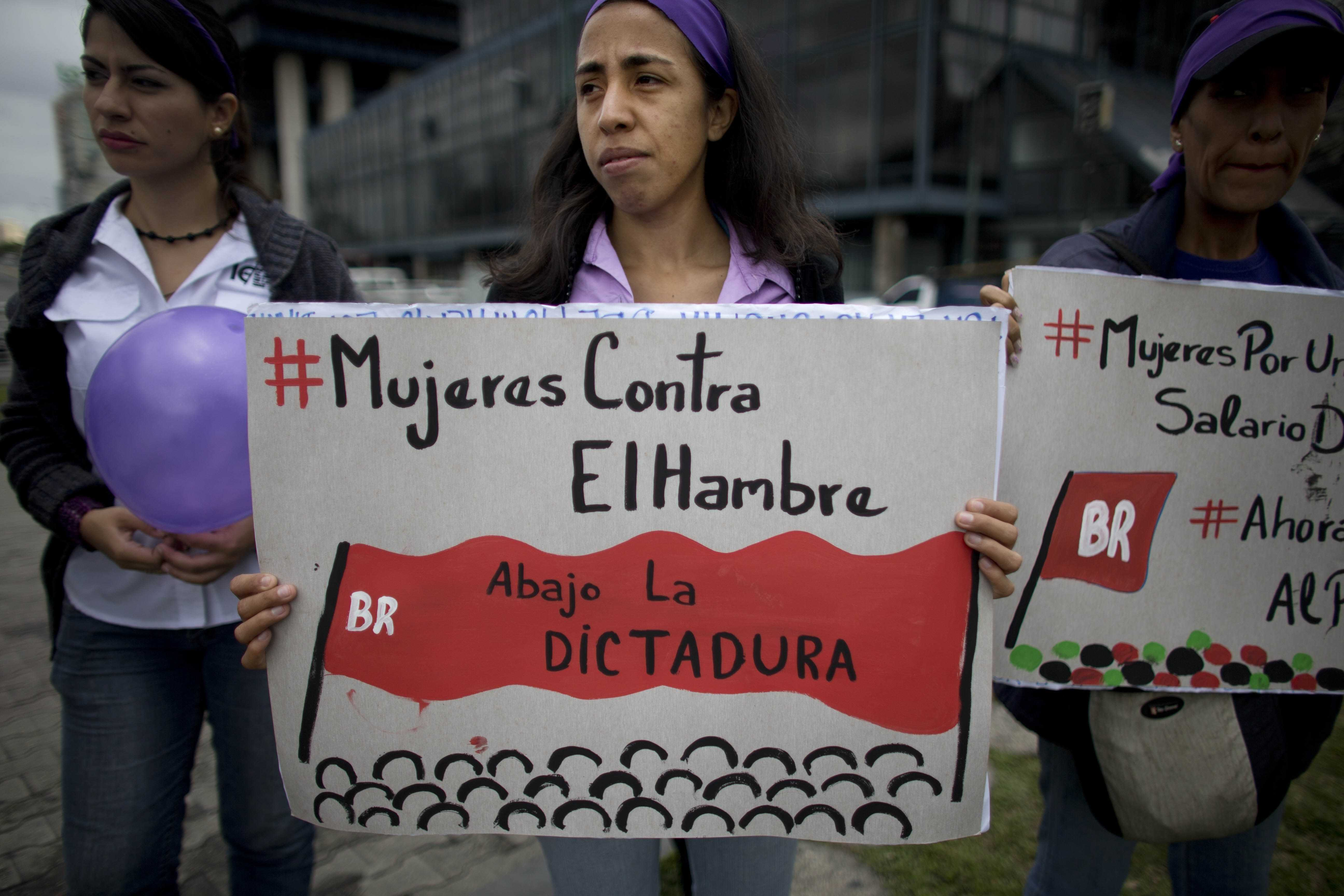 A woman holds up a sign that reads in Spanish