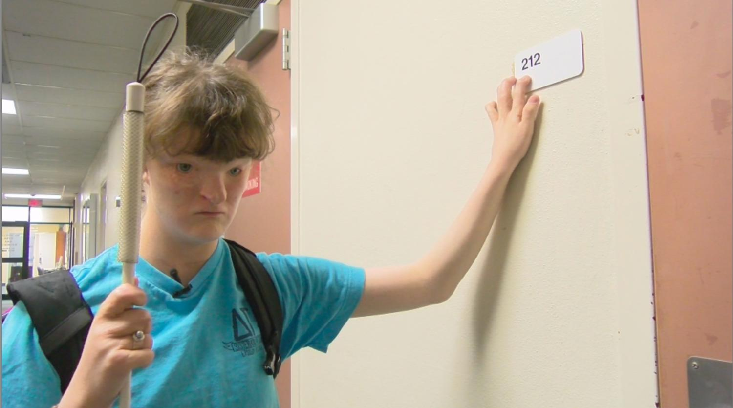 Sophie Trist, English writing freshman, uses the new Braille signs placed around to read.  After various complaints to campus disability services and talking with some peers involved in SGA, they were able to get Physical Plant to make new classroom signs that included Braille.