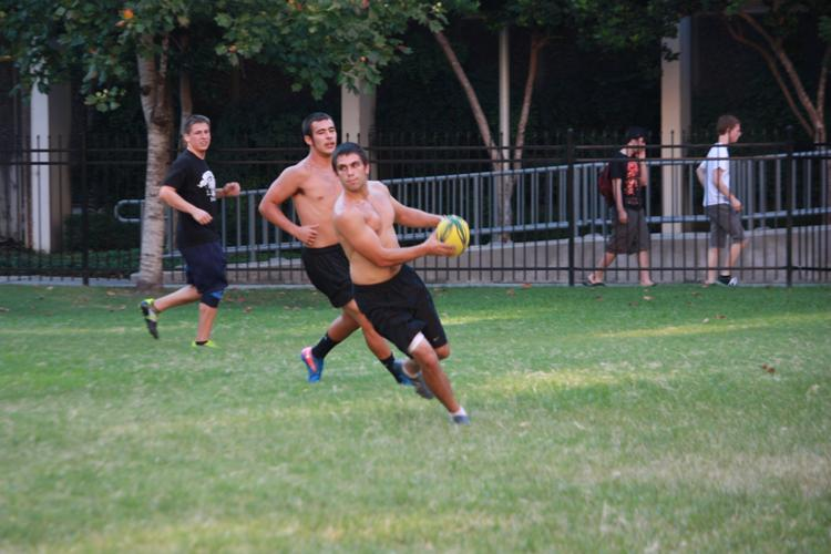 Finance senior Alex Weed moves the ball during rugby practice in the residential quad on Aug. 31. The team practices weekdays at 6 p.m.
