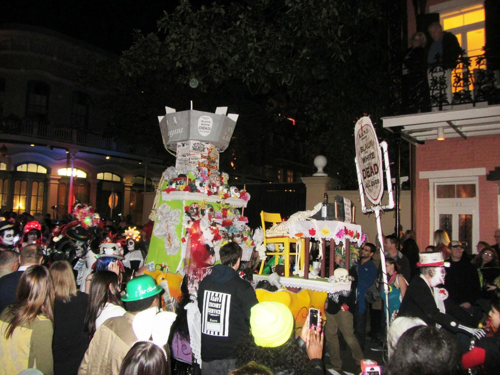 """Parade-goers surround a Krewe du Vieux float which criticizes the newspaper's recent decision to publish thrice weekly as opposed to daily. The float refers to the newspaper as """"The Times Prickayune"""" while calling it """"Black and White and Dead All Over."""