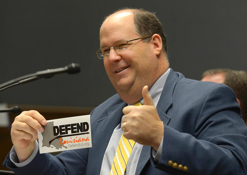 Rep. Jeff Thompson, R-Bossier City, holds up a sticker in response to questioning by Rep. Barbara Norton, D-Shreveport, during the House Criminal Justice Committee's discussion of House Bill 8 on Wednesday, April 17, at the Louisiana State Capitol in Baton Rouge