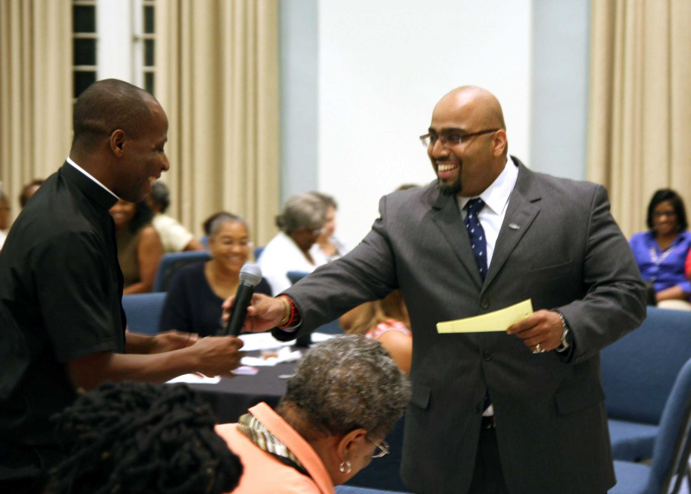 Reverend Etido Jerome (left) shares the microphone with Ansel Augustine (right) at a talk about faith and the youth on Thursday, Aug. 8.  Augustine has worked with youth organizations since 2002 after he graduated from Loyola two years prior.