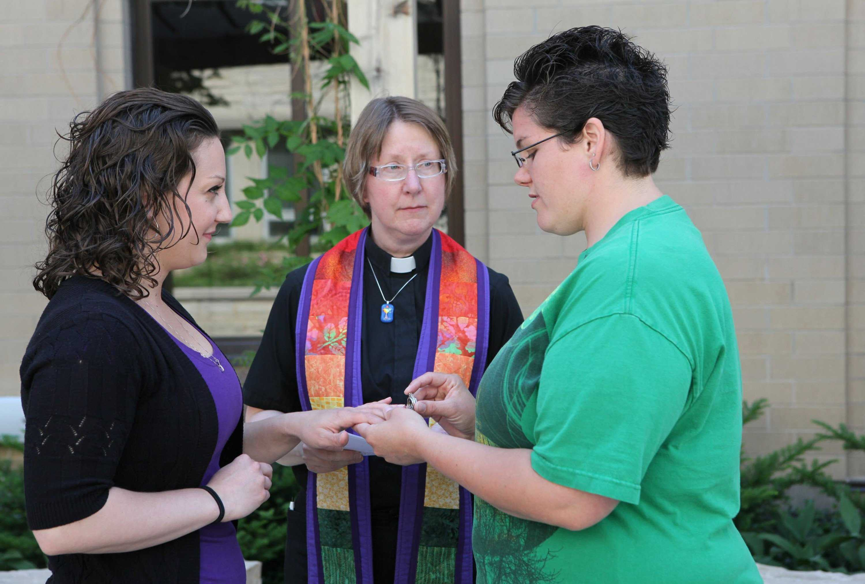 Courtney Beckwith, left, and Amber Beckwith are married by Rev. Lori Hlaban on Monday, June 9, 2014, in Waukesha, Wisc. The couple had their names changed legally after an earlier commitment ceremony.