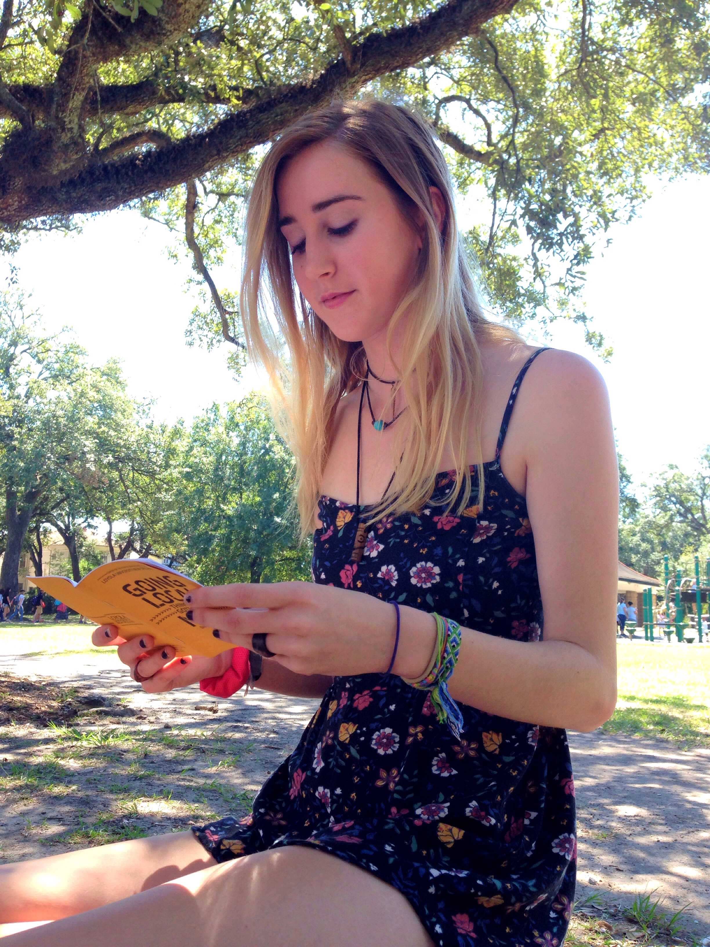 Charlotte Preuss, mass communication freshman, reads over the Nola Bucket List guidebook. The guidebook is intended for newcomers who are looking to explore the city. Photo credit: Zayn Abidin