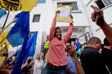 Newly elected opposition congresswoman Marialbert Barrios holds up her credentials as lawmaker, from the National Electoral Council (CNE) in Caracas, Venezuela, Wednesday, Dec. 9, 2015, after congressional elections. The Democratic Unity opposition coalition secured, by a single seat, a two-thirds supermajority, surpassing its even most-optimistic forecasts. (AP Photo/Fernando Llano)