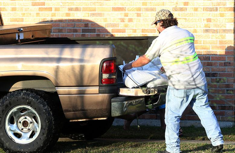 A+man+unloads+sand+bags+from+his+truck+to+place+around+his+home+in+Slidell%2C+Louisiana+on+Monday%2C+March+14%2C+2016.+Residents+in+Slidell+were+concerned+about+flooding+in+the+area+after+a+weekend+of+heaving+rain+and+flooding+across+Louisiana+and+the+Pearl+River+cresting.