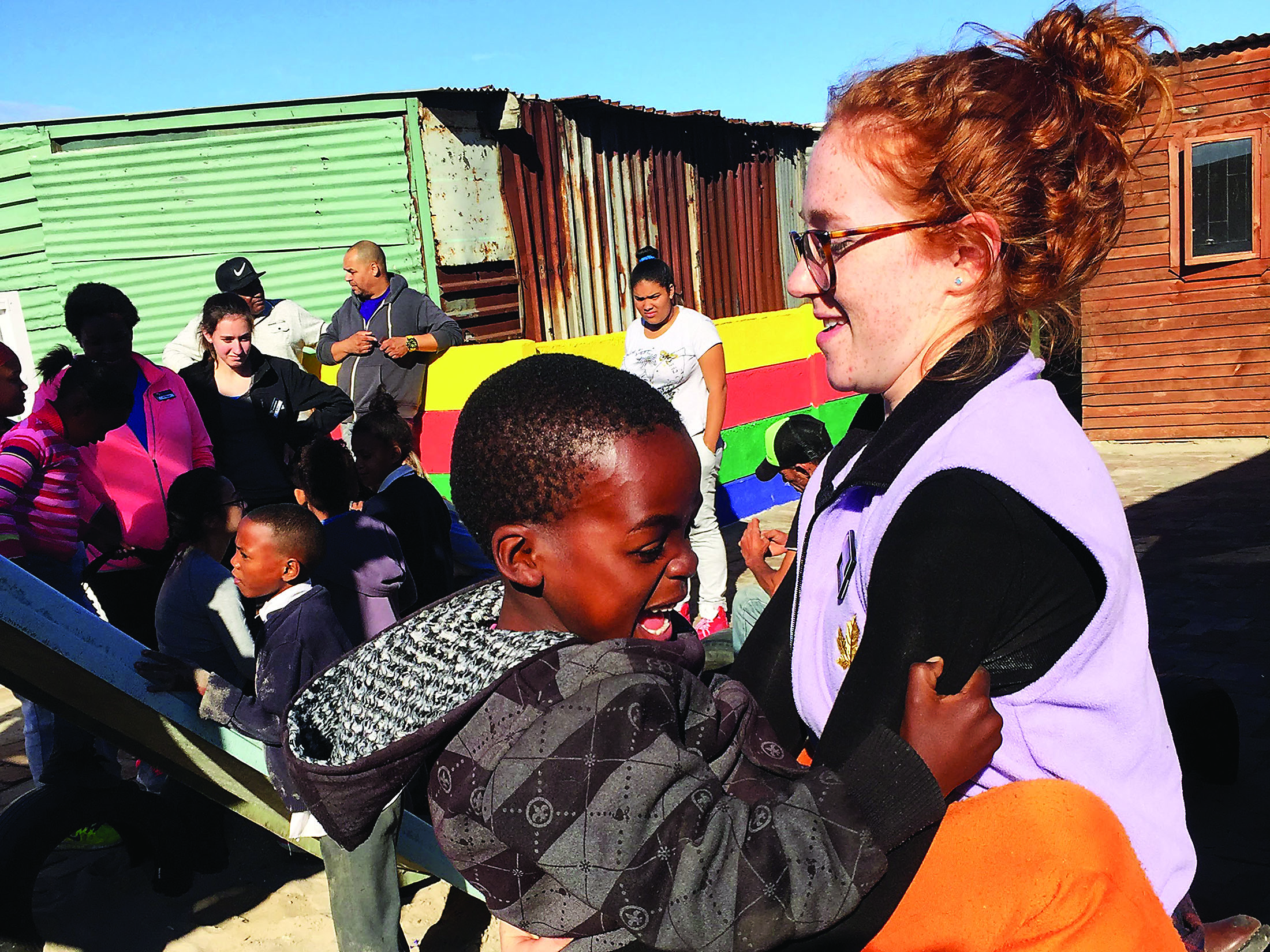 Emily Mastin A'16 plays with a child in South Africa. Mastin worked there with Iggy Vols this summer. (Image credit: Emily Mastin)