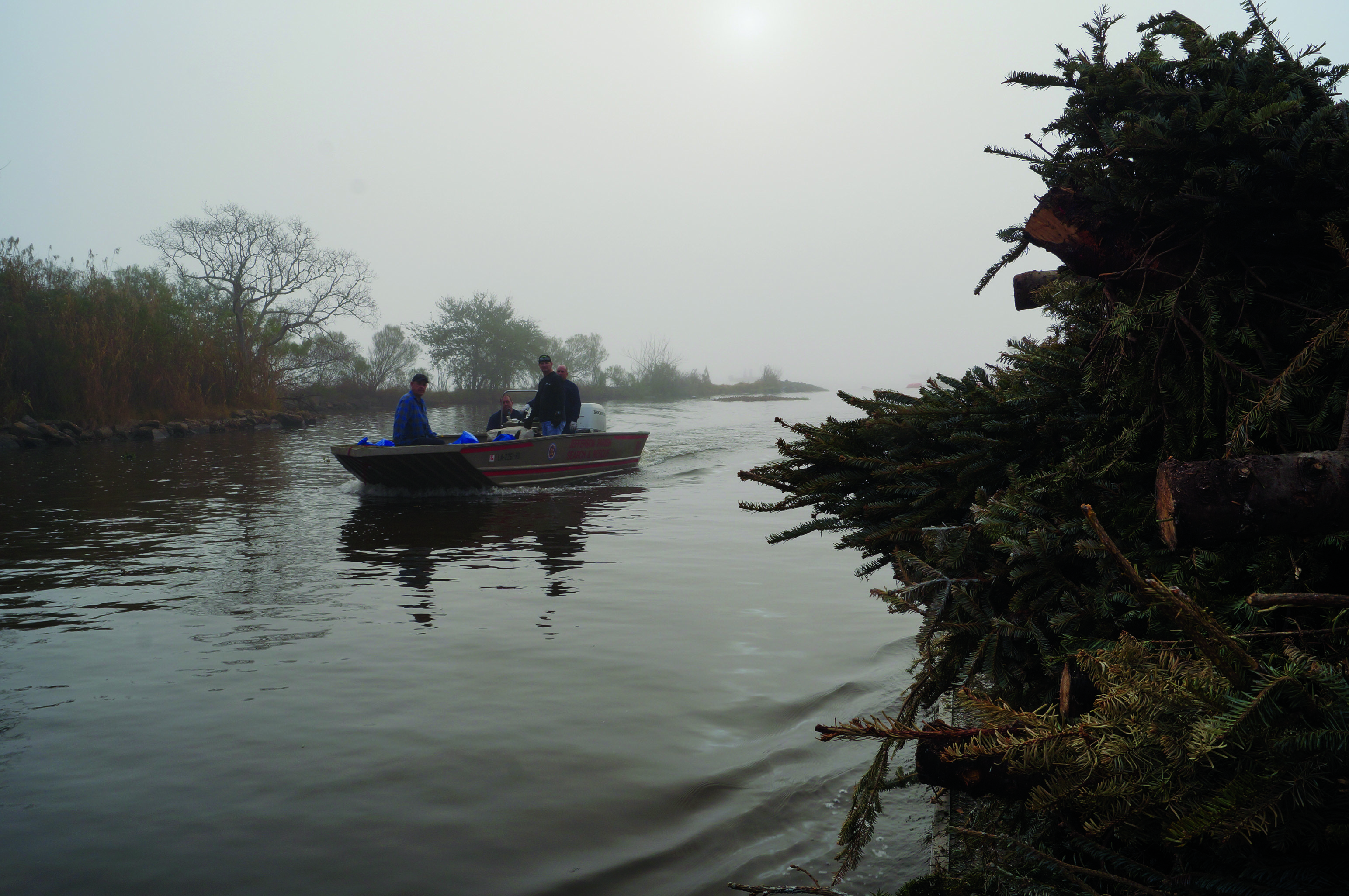 A+boat+of+volunteers+returns+to+Cochiaras+Marina+in+Lafitte%2C+Louisiana%2C+Jan.+14%2C+after+dropping+trees+into+special+%22cribs%22+in+the+bayou.+The+Christmas+trees+break+the+waves+in+the+area%2C+slowing+coastal+erosion+and+rebuilding+marshland.+Photo+credit%3A+Colleen+Dulle