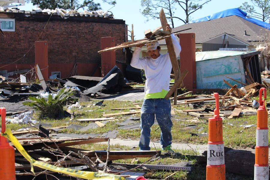 A+worker+with+Mr.+Fix+It+helps+to+pile+up+the+debris+left+after+the+storm.+Shortly+after+the+storm%2C+volunteers+from+all+over+came+to+aid+those+affected+by+the+storm.