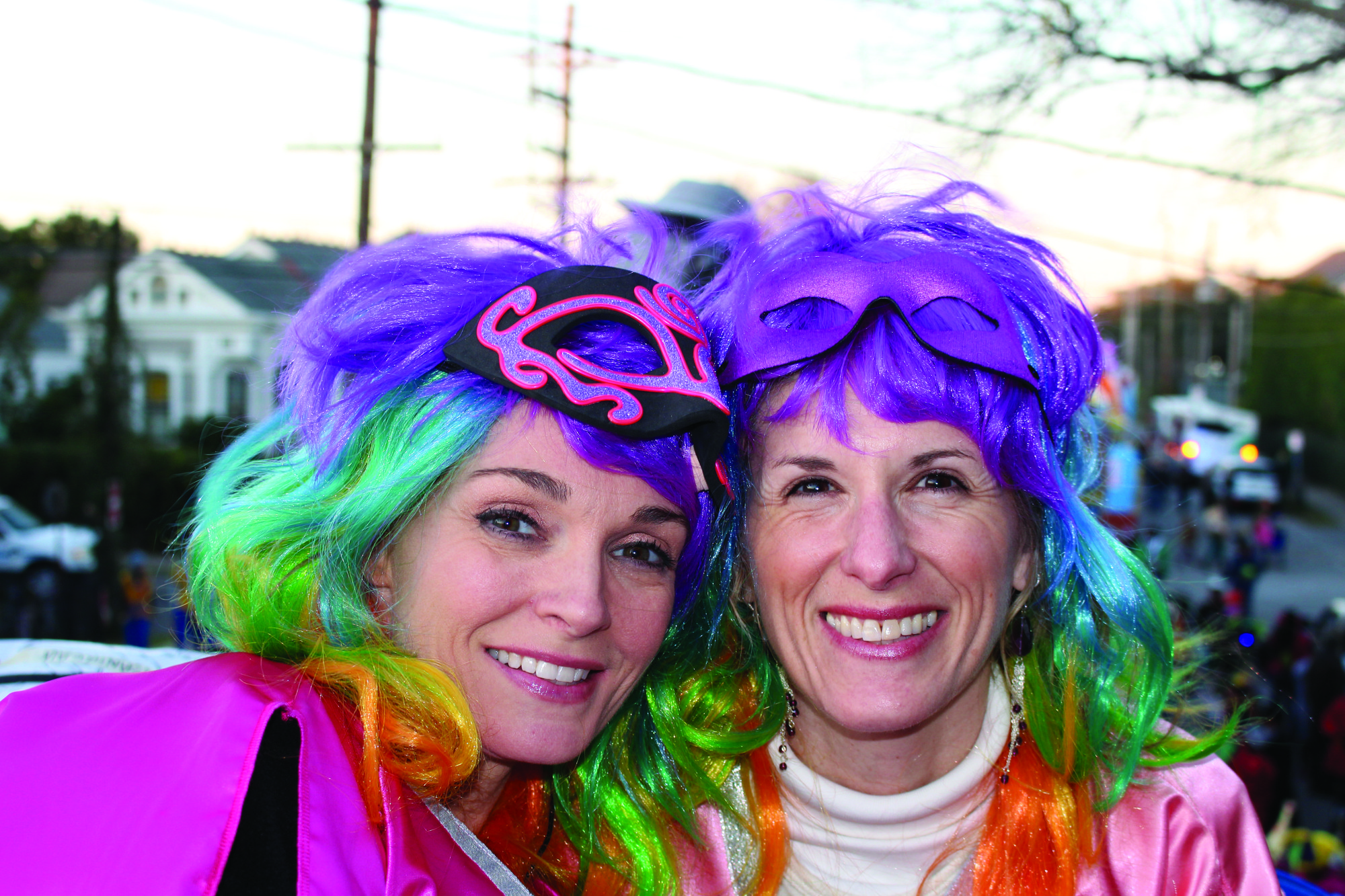 Jennifer Jeanfreau (right) and friend at a previous Mardi Gras. Both ready to ride in Muses wearing colorful wigs and smiles.