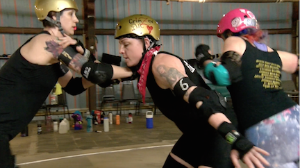 CrimZen Doll, a Big Easy Roller Girl, practices blocking on the rink.