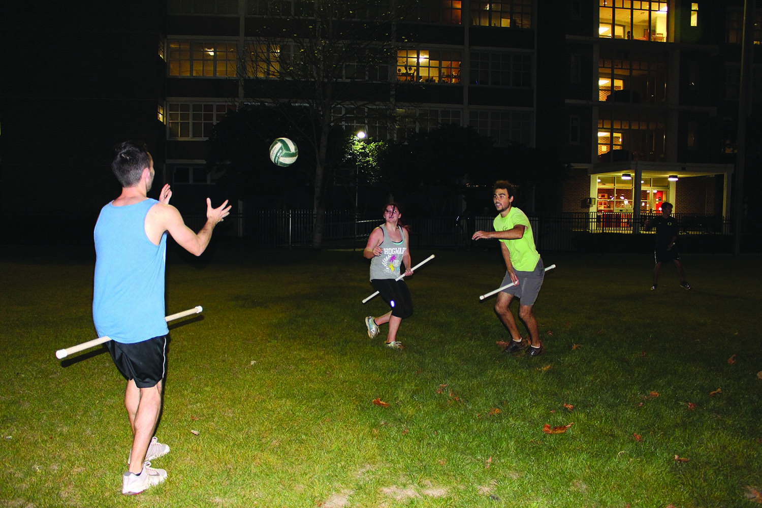 Jeremy Gretzer, theater sophomore and team captain (left), receives a pass from Sebastian Gomez (right), biology sophomore and team captain, as Shannon Garrety, english and business freshman defends (middle). The quidditch team is currently training and recruiting to prepare for next season. Photo credit: Alliciyia George