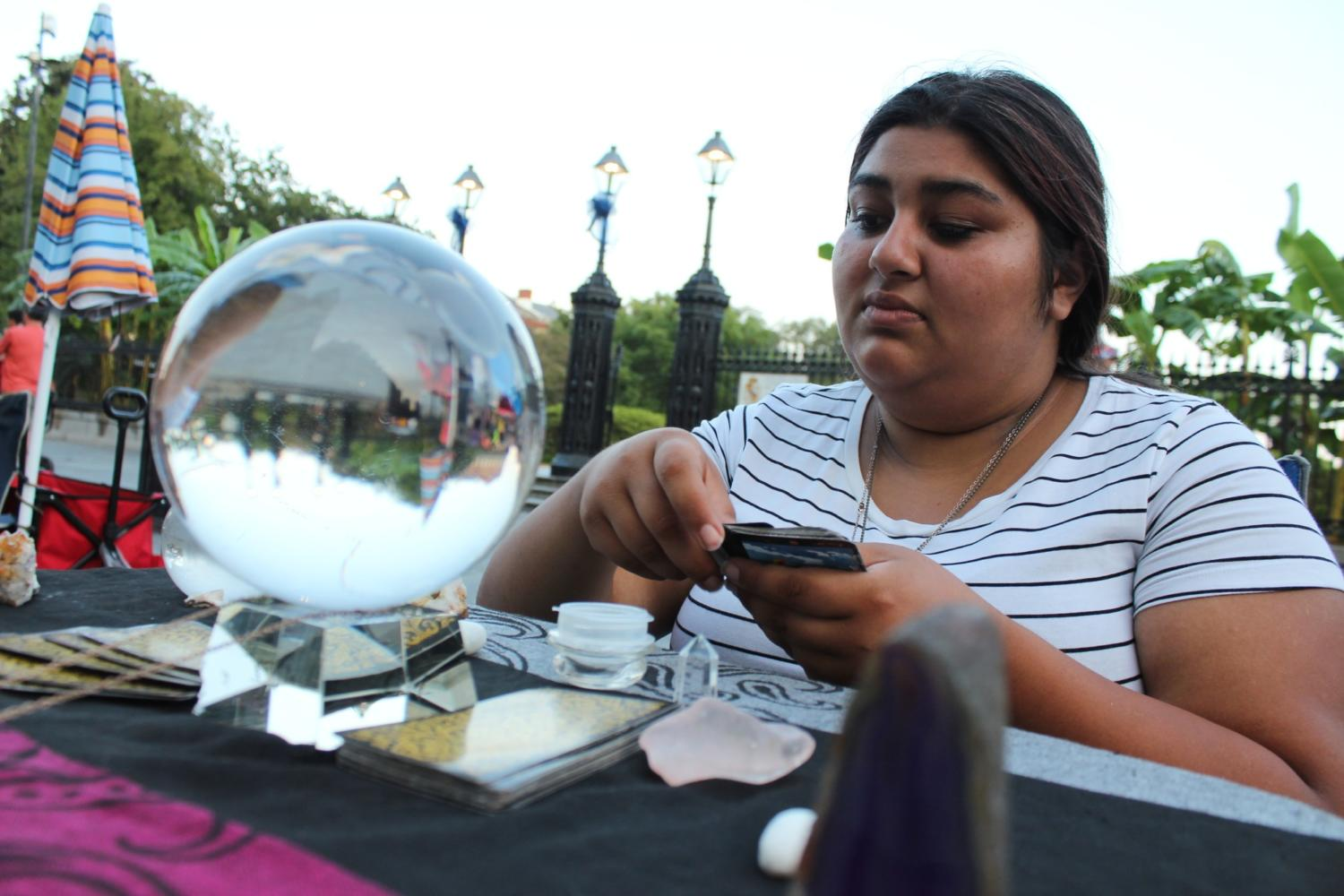Fortune teller Miss Stephanie deals out tarot cards near her crystal ball Photo credit: Cristian Orellana