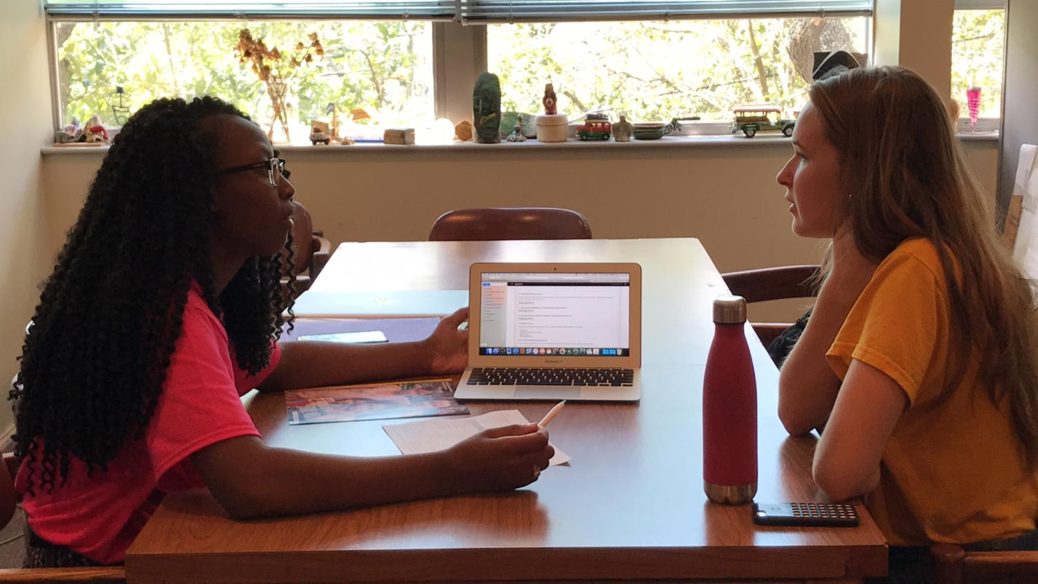 Rodriana Edwards, right, shows Nicole Bouchie, environmental science sophomore, different study abroad programs for Japan. Loyola's Center for International Education provides peer advisors to aid students who are interested in traveling while in college. Photo credit: Chasity Pugh