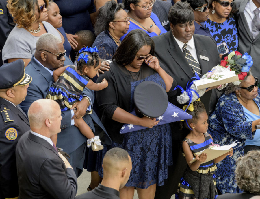 Brittiny+McNeil+holds+the+hat+and+flag+of+her+late+husband+New+Orleans+Police+Officer+Marcus+McNeil+while+she+is+comforted+by+her+daughter+Camille+McNeil%2C+2%2C+left%2C+next+to+her+other+daughter%2C+Maisie+McNeil%2C+5%2C+bottom+right%2C+and+McNeil%27s+mother+Kimberly+McNeil%2C+top+right%2C+and+his+grandmother+Alvena+McNeil+at+Mount+Olivet+Cemetery+during+his+funeral+in+New+Orleans%2C+La.%2C+Saturday%2C+Oct.+21%2C+2017.+New+Orleans+Police+Department+Superintendent+Michael+Harrison%2C+left%2C+and+Mayor+Mitch+Landrieu%2C+second+left%2C+stand+with+hands+over+their+hearts.+McNeil%2C+29%2C+was+shot+and+killed+Oct.+13+during+a+routine+patrol.+%28Matthew+Hinton%2FThe+Advocate+via+AP%29+Photo+credit%3A+Associated+Press