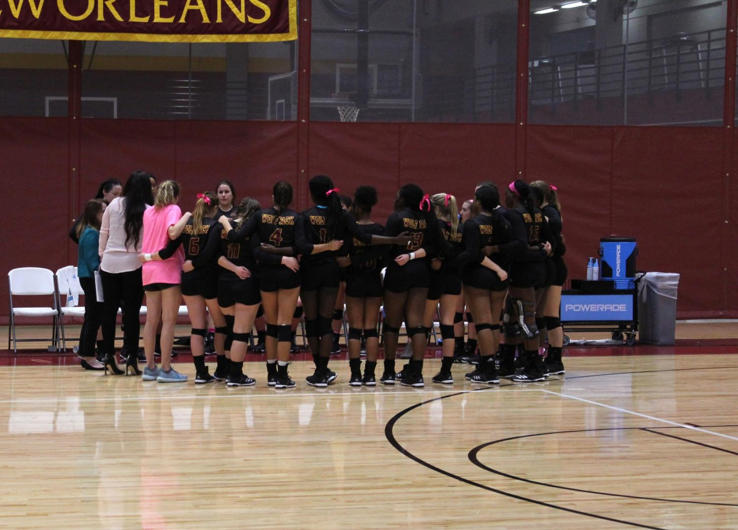 The Loyola volleyball team gathers in a group huddle during the game. The 2017 Loyola volleyball team plans to compete against the 2002 volleyball team on January 19 at 7pm at the Den. Photo credit: Cristian Orellana