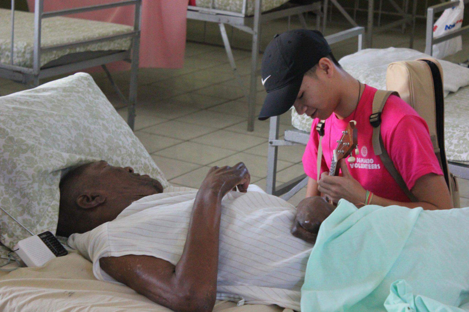 Calvin Tran, music therapy senior, plays ukulele for a patient at St. Teresa's Home for the Destitute and Dying in Kingston, Jamaica, during the Ignacio Volunteer trip December 2017. Photo credit: Lily Cummings