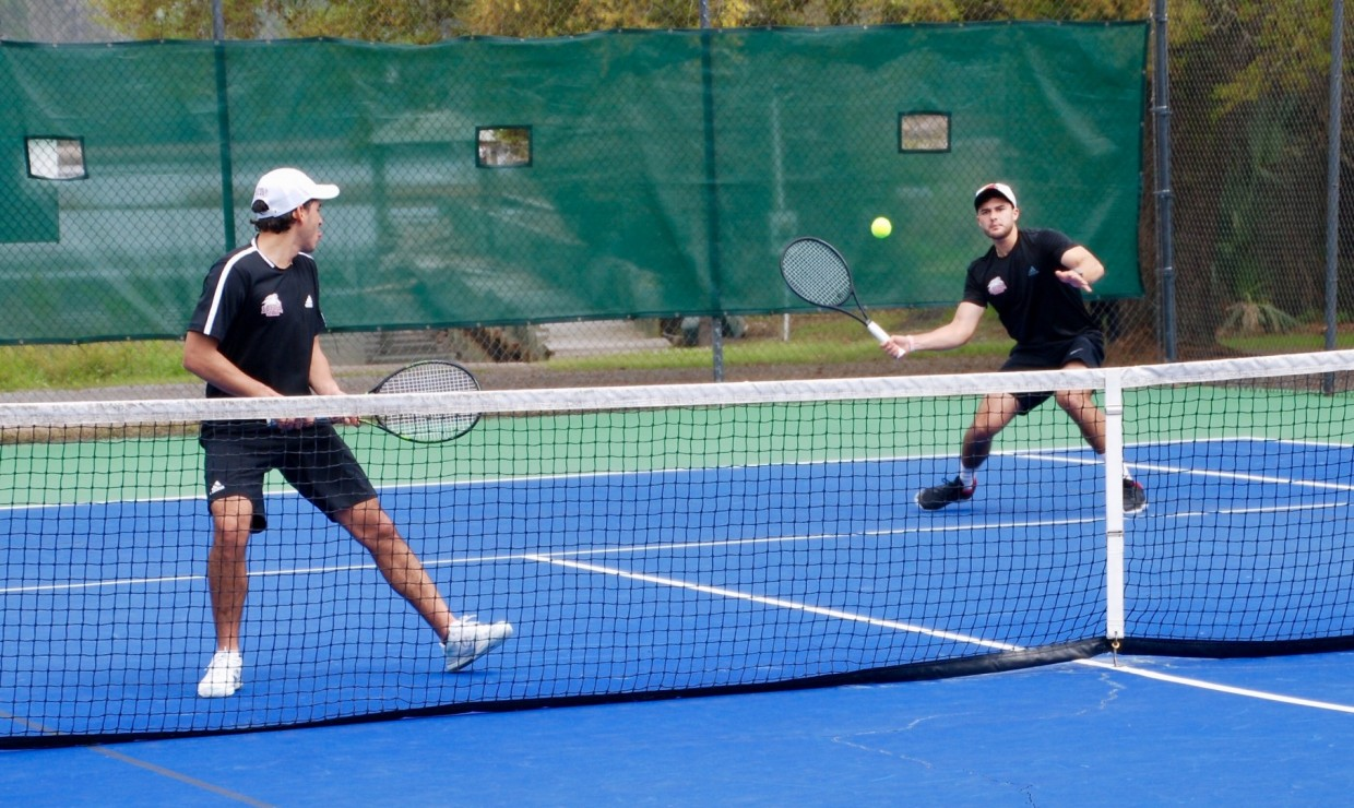 Loyola men's tennis players competing in a doubles match. Both the men's and women's teams went undefeated in their five-game stretch over Spring Break. Photo credit: Loyola University Athletics