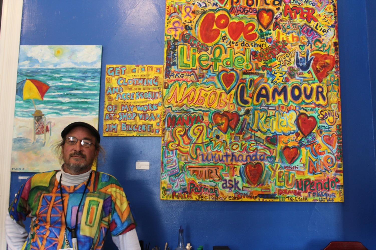 Artist Jim Bilgere poses in front of his paintings which are displayed on the walls of Café Luna. Photo credit: Catie Sanders
