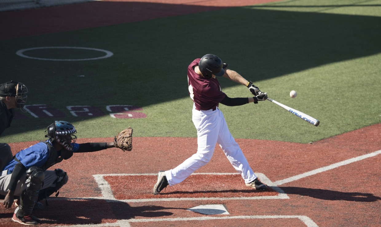 Ben Condara (14), general studies business senior, sinks a ball into left field. Loyola took one win versus No. 11 William Carey University. Photo credit: Loyola University Athletics