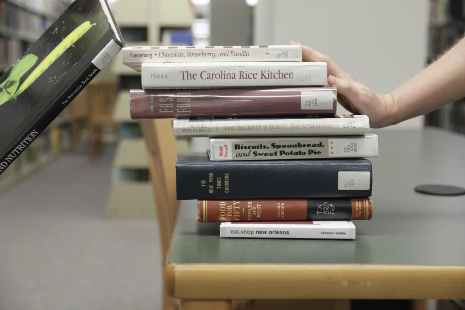 Julia Gollobit, food studies junior, pushes food studies books of a desk in Monroe Library. After its first year in existence, the food studies program was suspended for the 2018-2019 school year and its future remains uncertain. Photo credit: Cristian Orellana