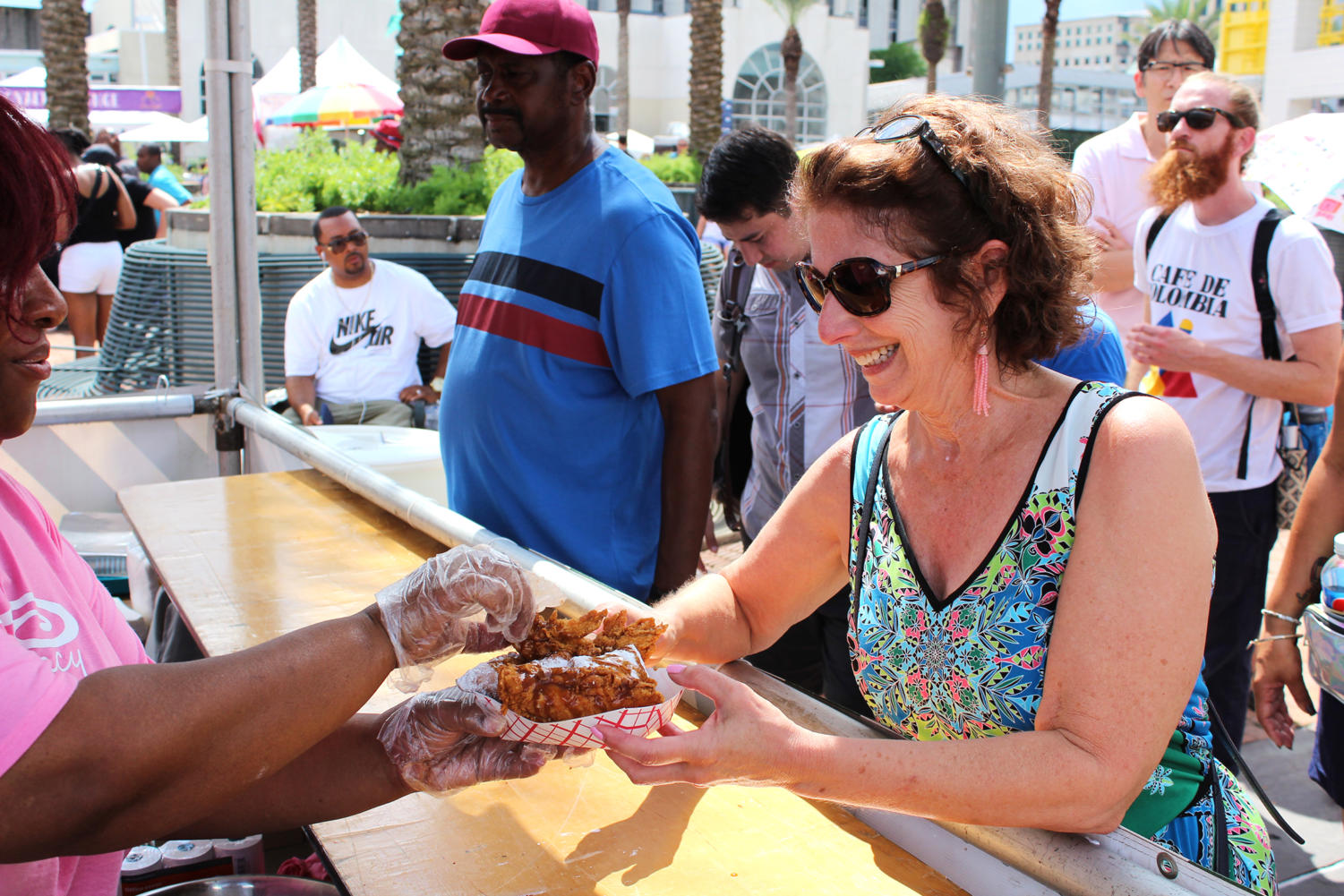 Fried Chicken Fest atendee buys fried chicken and beignets from Sweet Legacy Tent.