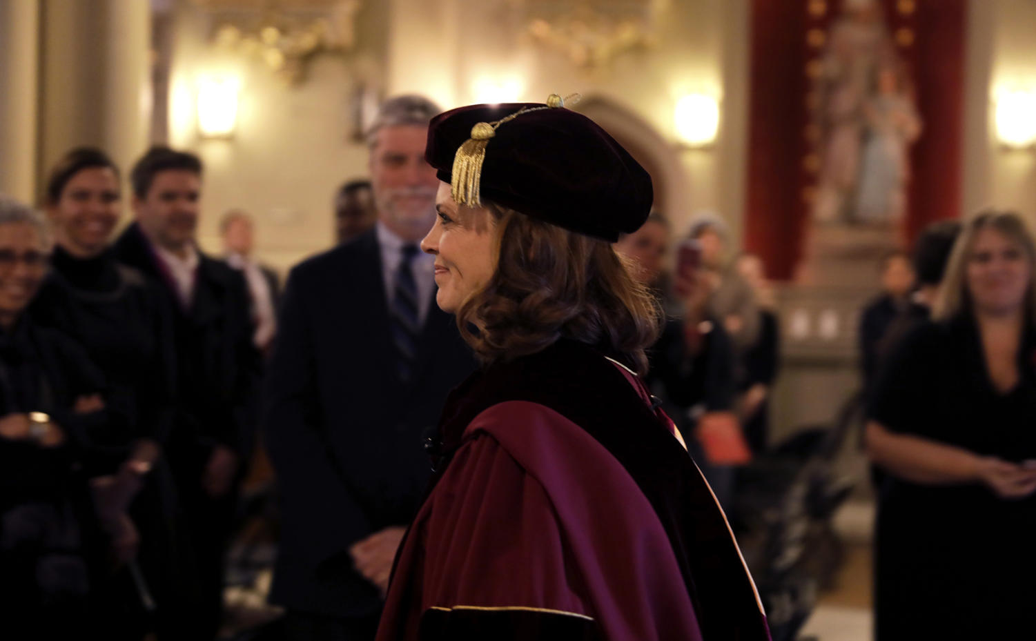 President Tania Tetlow walks into Holy Name of Jesus church dressed in academic regalia. Photo credit: Angelo Imbraguglio