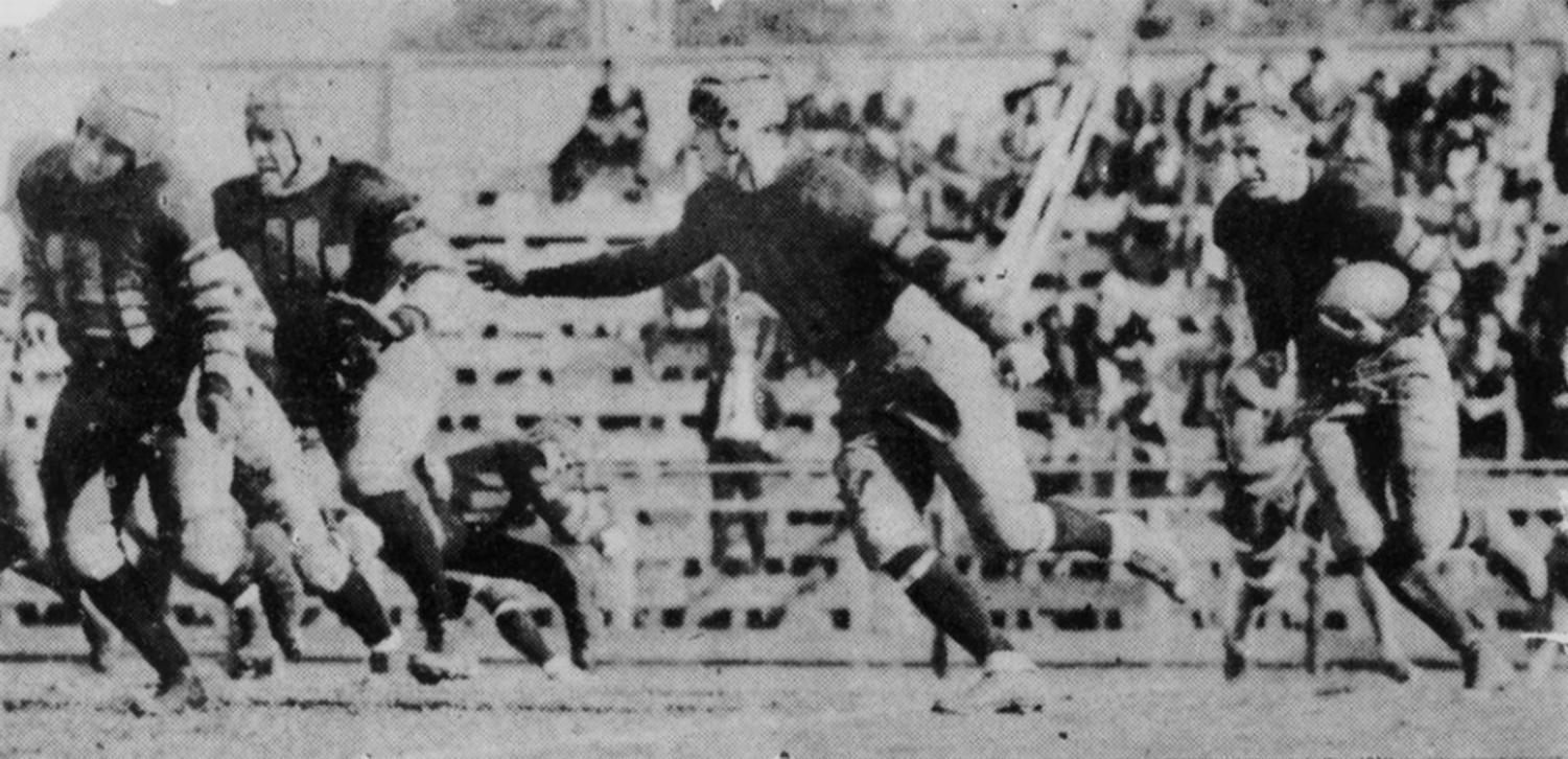 Here is an example of the airtight interference given Buck Moore on his long runs. Much praise has been showered on Buck for the manner in which he has broken loose in every game for sensational dashes, and just as much is due his interferers. The photo, snapped during the Lincoln game, shows Charlie Jaubert at the extreme left, Don Maitland next behind him, and Red Gremillion in front of Moore.