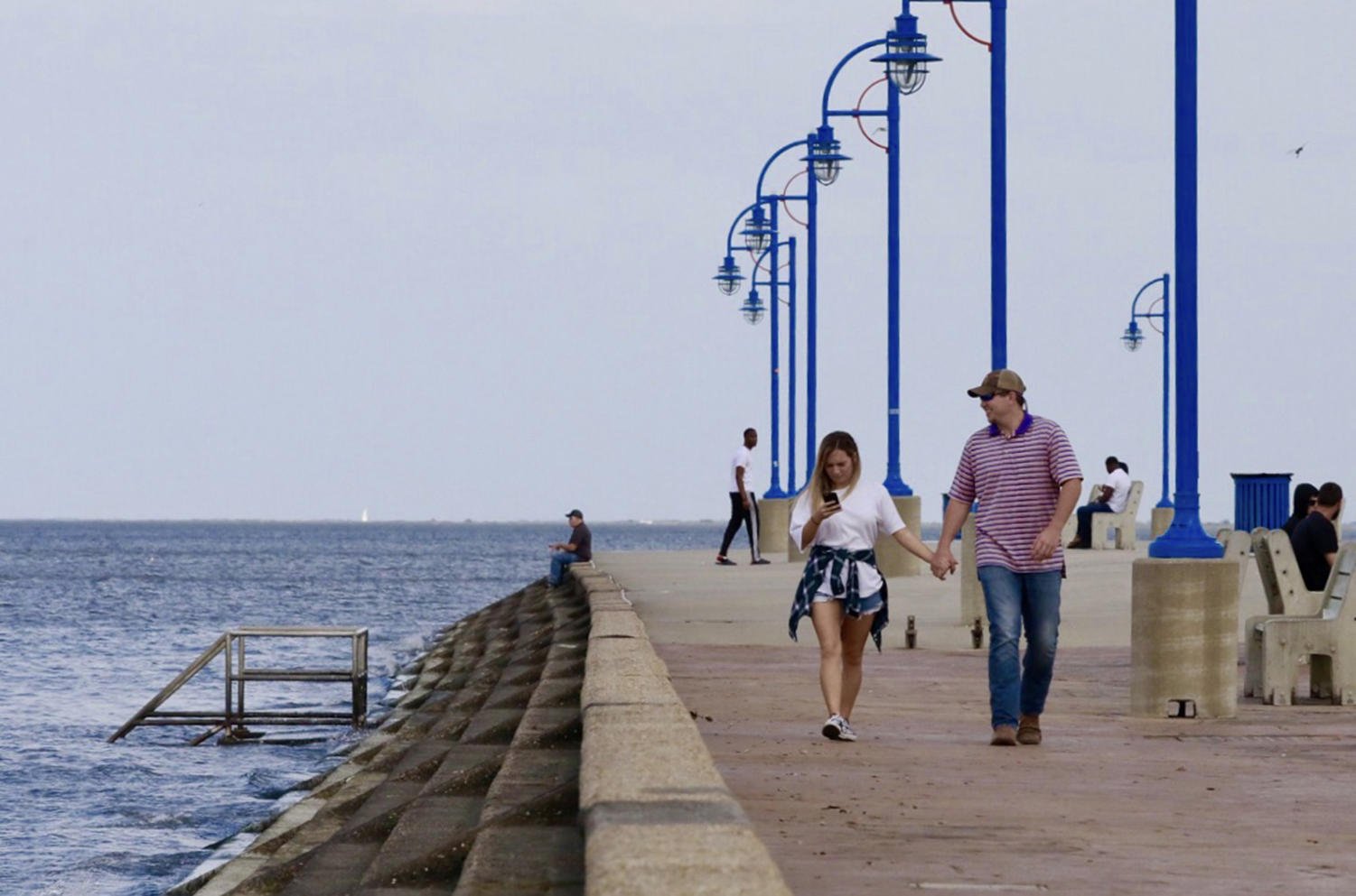 A couple strolls along the sidewalk by Lake Pontchartrain. The site is frequented by residents for its natural beauty. Photo credit: Andres Fuentes
