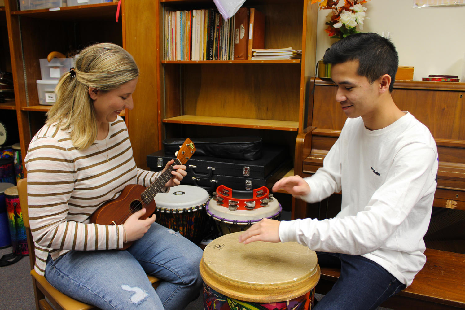 Music therapy seniors Katarina Prasso (left) and Calvin Tran (right) practice playing instruments Wednesday in the department's music lab. Music therapy majors are required to proficiently play a variety of instruments used in therapeutic sessions. Photo credit: India Yarborough