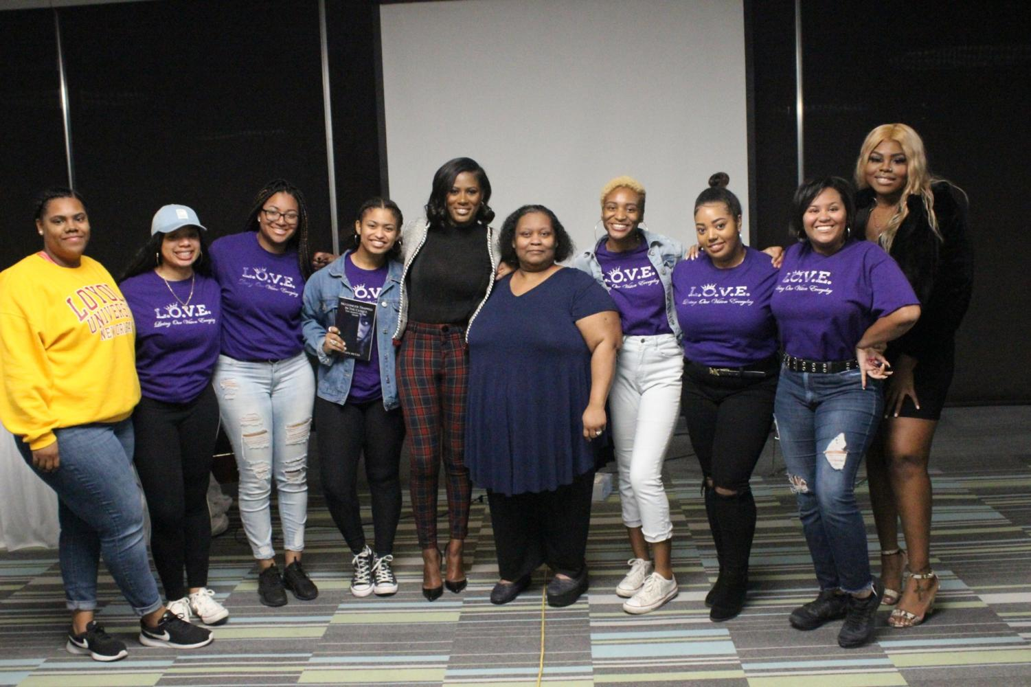 Members of Loyola's L.O.V.E. chapter pose with author Asante McGee on Jan. 29. McGee spoke about her experiences with R. Kelly and abuse. Photo credit: Maia Moses