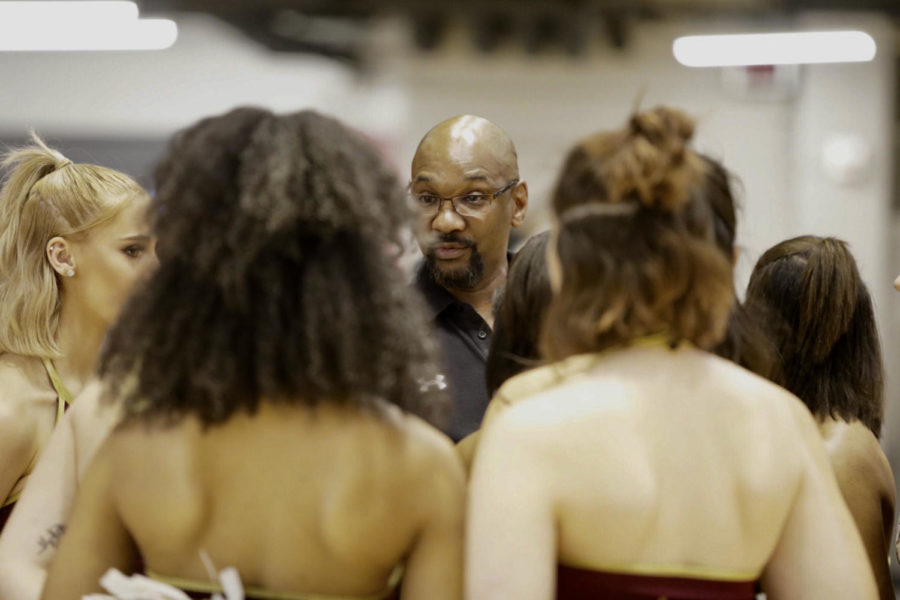Cheer+and+dance+head+coach+Rickey+Hill+addresses+the+dance+team+before+a+basketball+game.