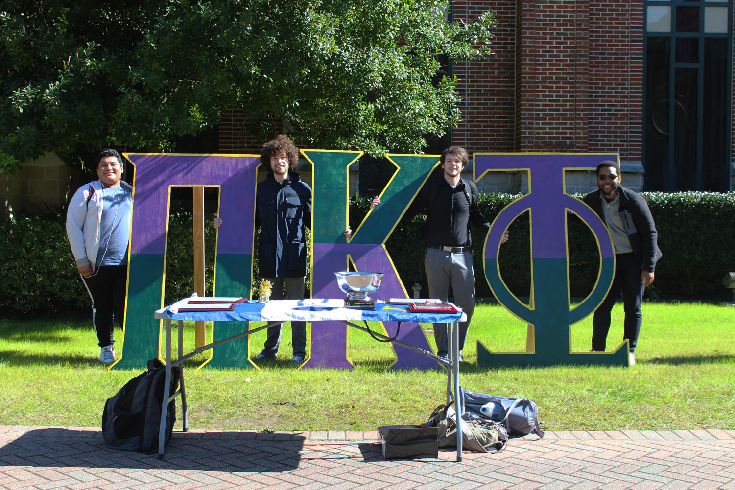 Joseph Sabados, Spencer Stingley, Hunter Cobb, Isaiah Jones (from left to right), brothers of Pi Kappa Phi, are tabling during recruitment week. Photo credit: Cristian Orellana