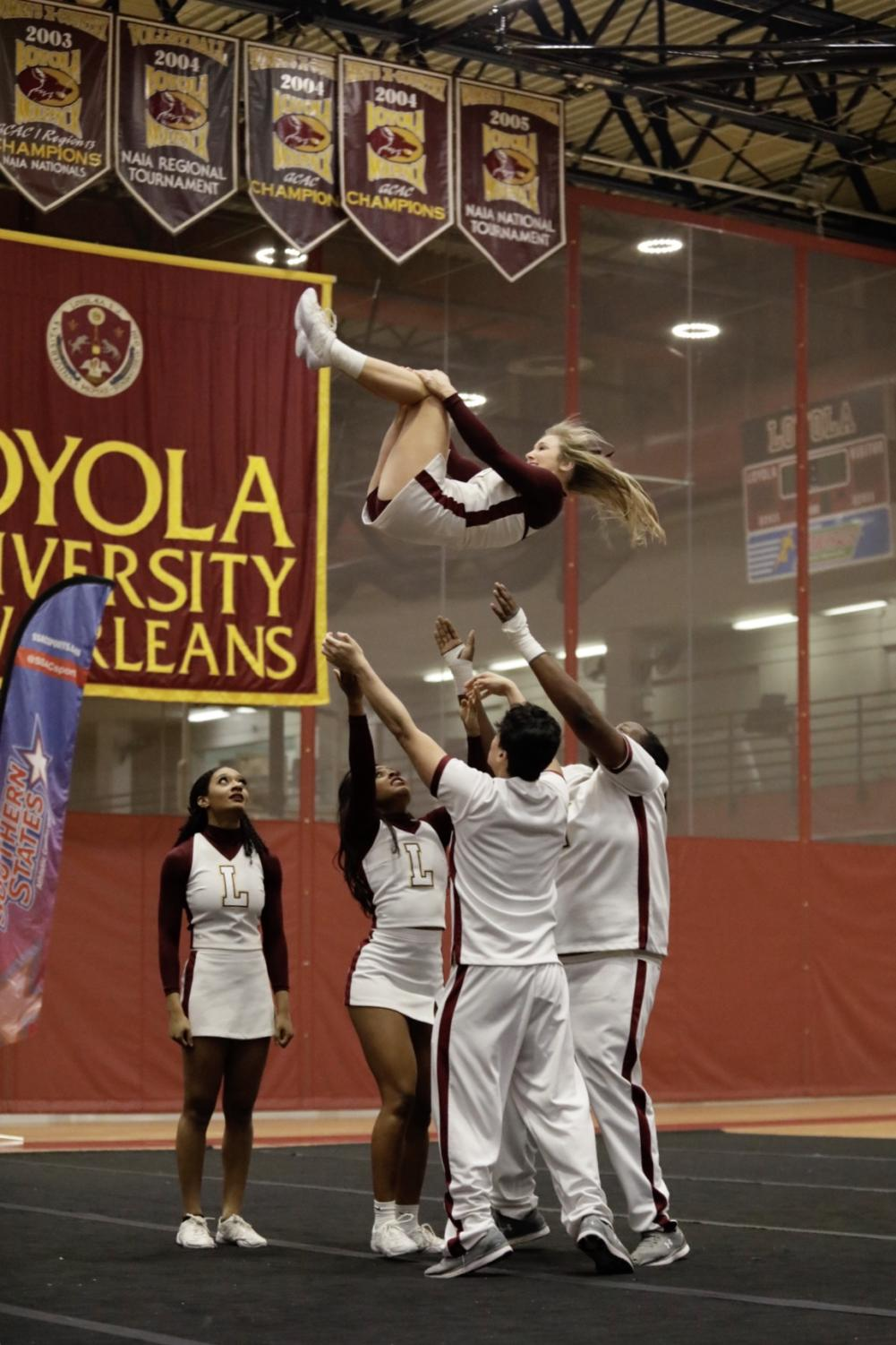 Loyola%27s+cheer+team+tosses+up+a+cheerleader+during+their+routine.+Photo+credit%3A+Ariel+Landry