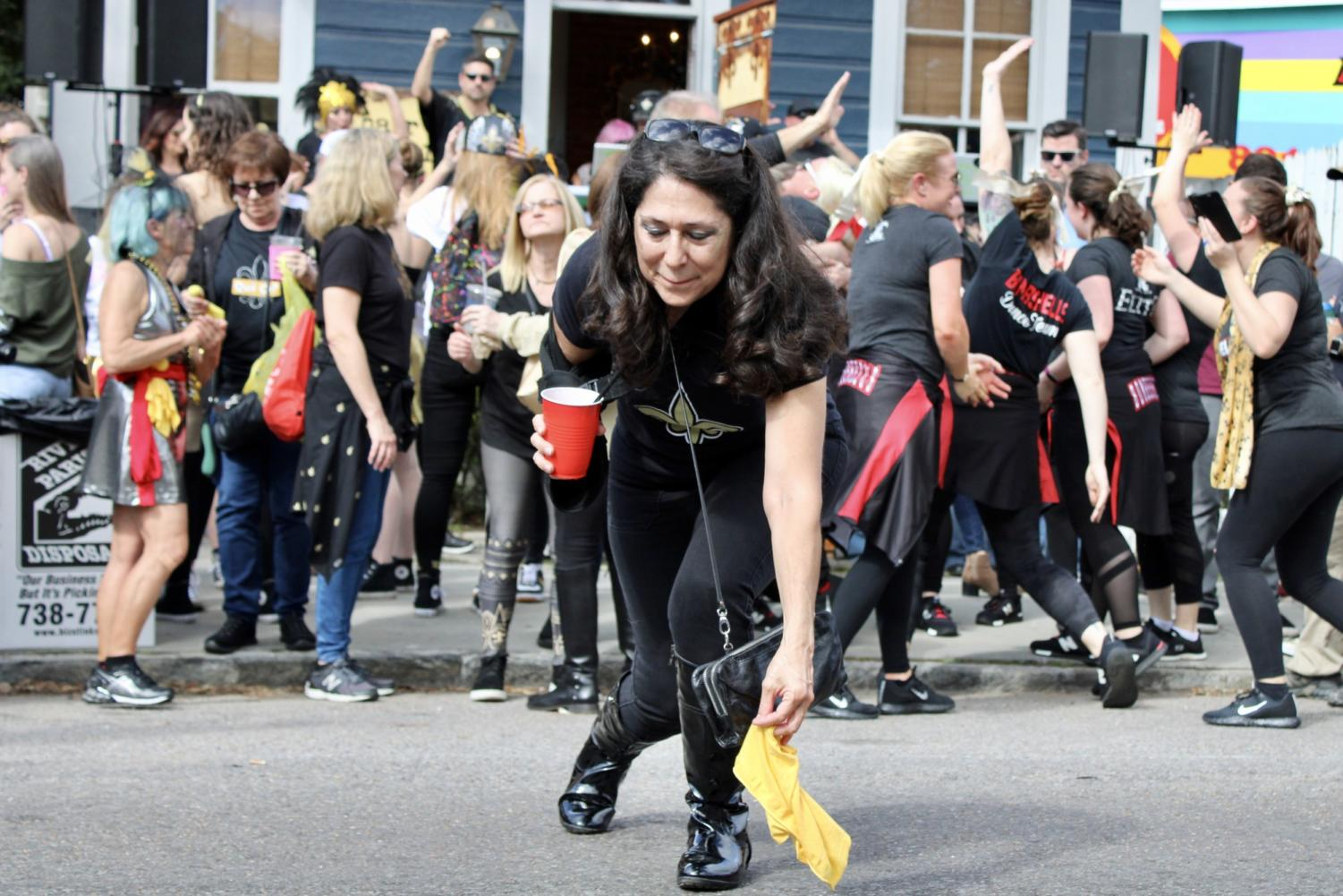 A Saints fan picks up a thrown flag at the Magazine Street block party. Photo credit: Madison Mcloughlin