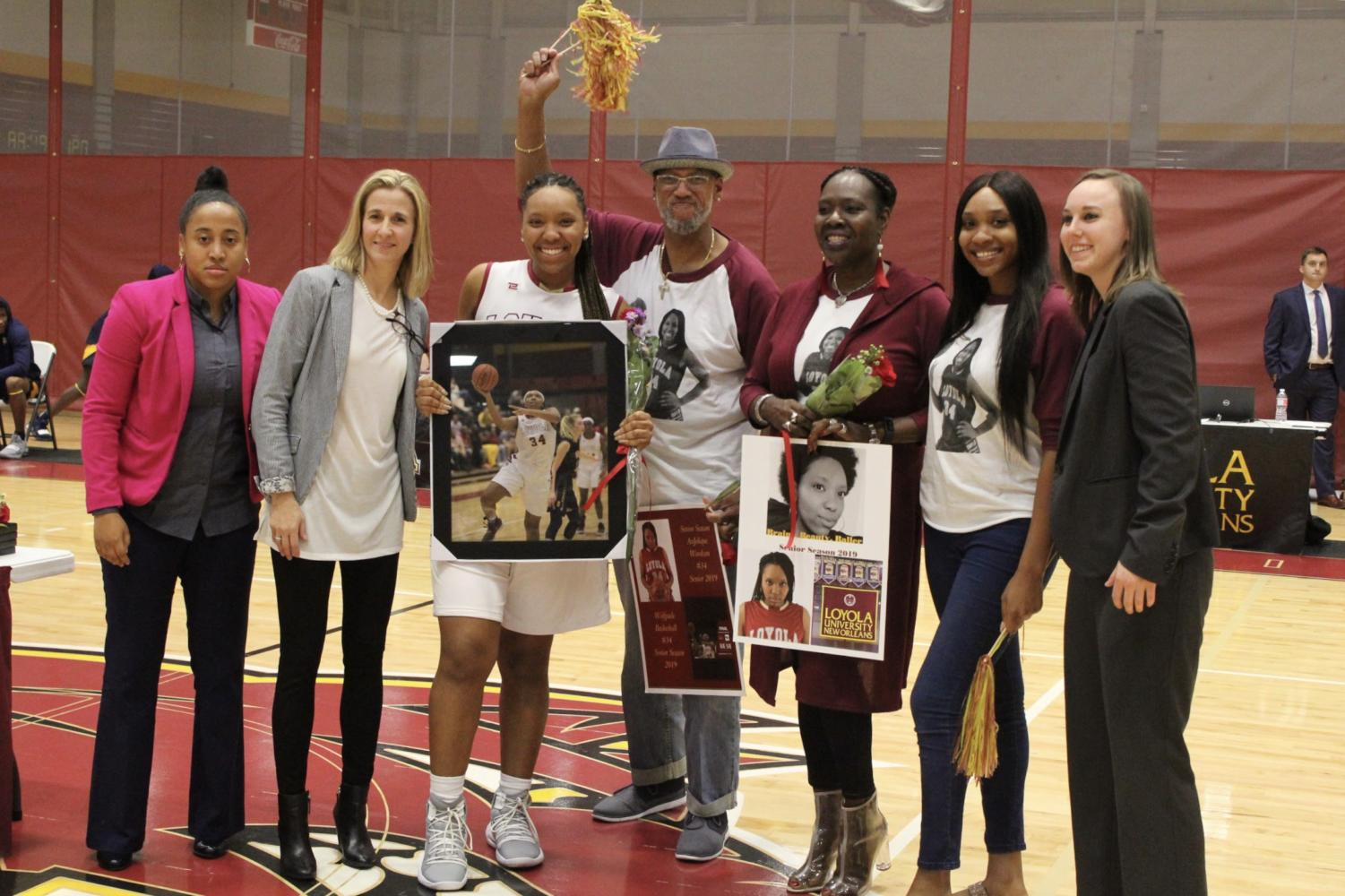 Biology+senior+An%27Jolique+Woodson+poses+with+her+family+and+the+women%27s+basketball+coaching+staff.