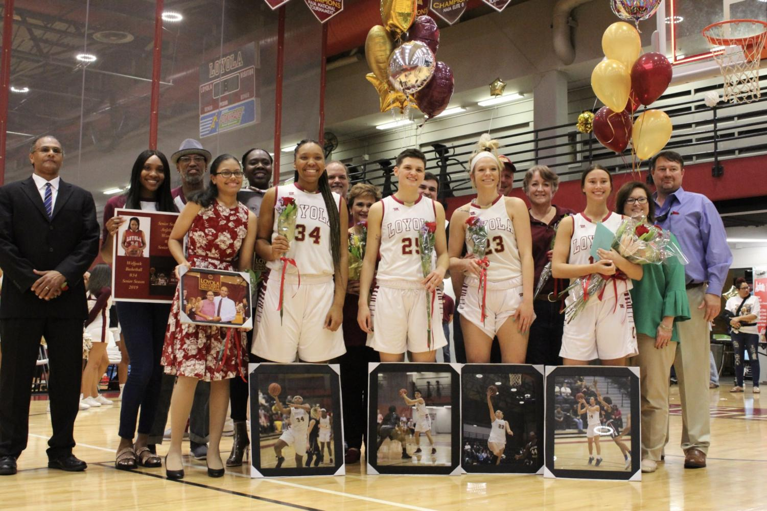 All+senior+members+of+the+women%27s+basketball+team+pose+with+their+families+at+Senior+Night.+Photo+credit%3A+Rosha%27E+Gibson