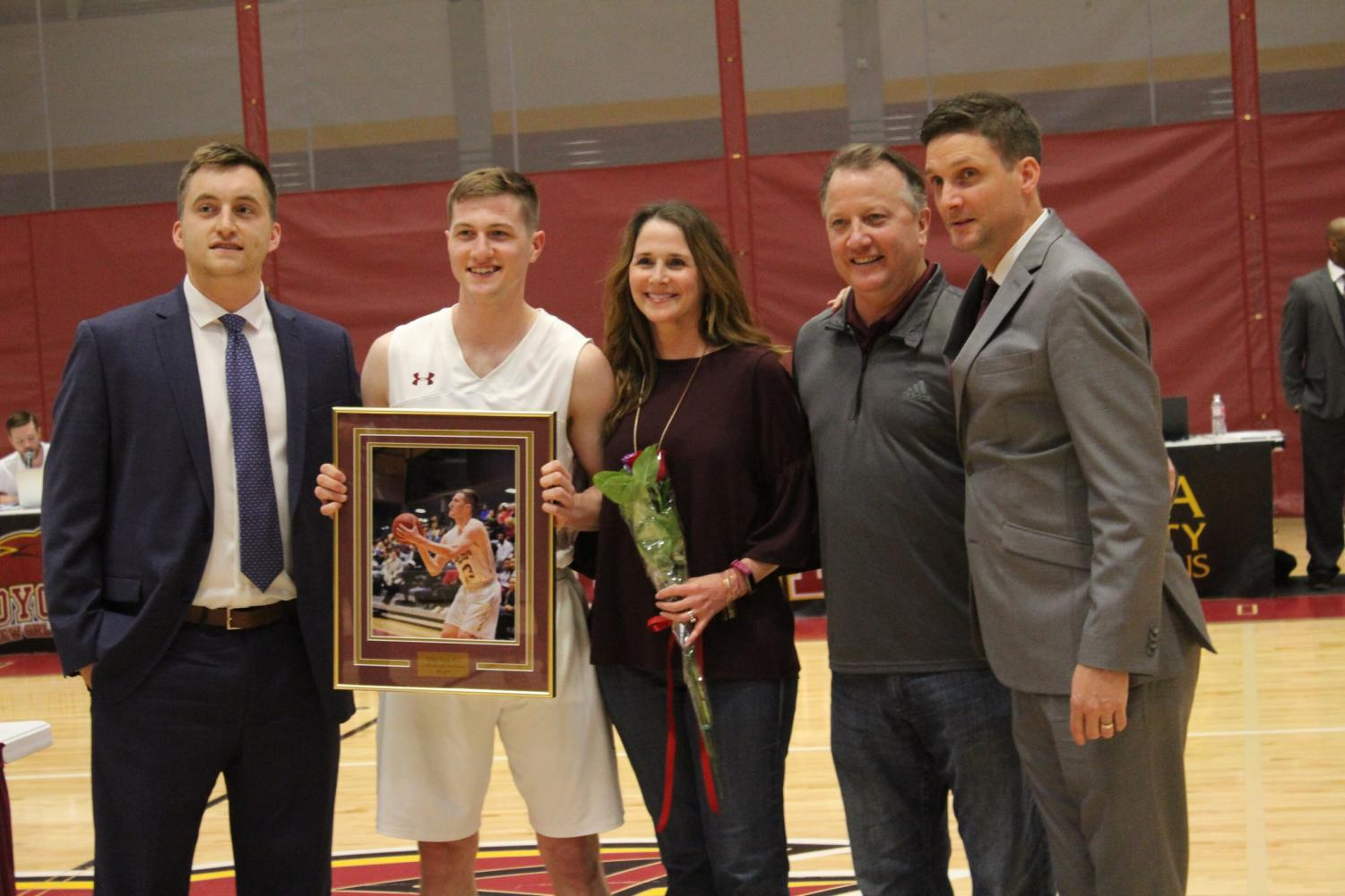 Finance+senior+Ethan+Turner+%2833%29+joins+his+family+and+the+coaching+staff+for+a+photo.