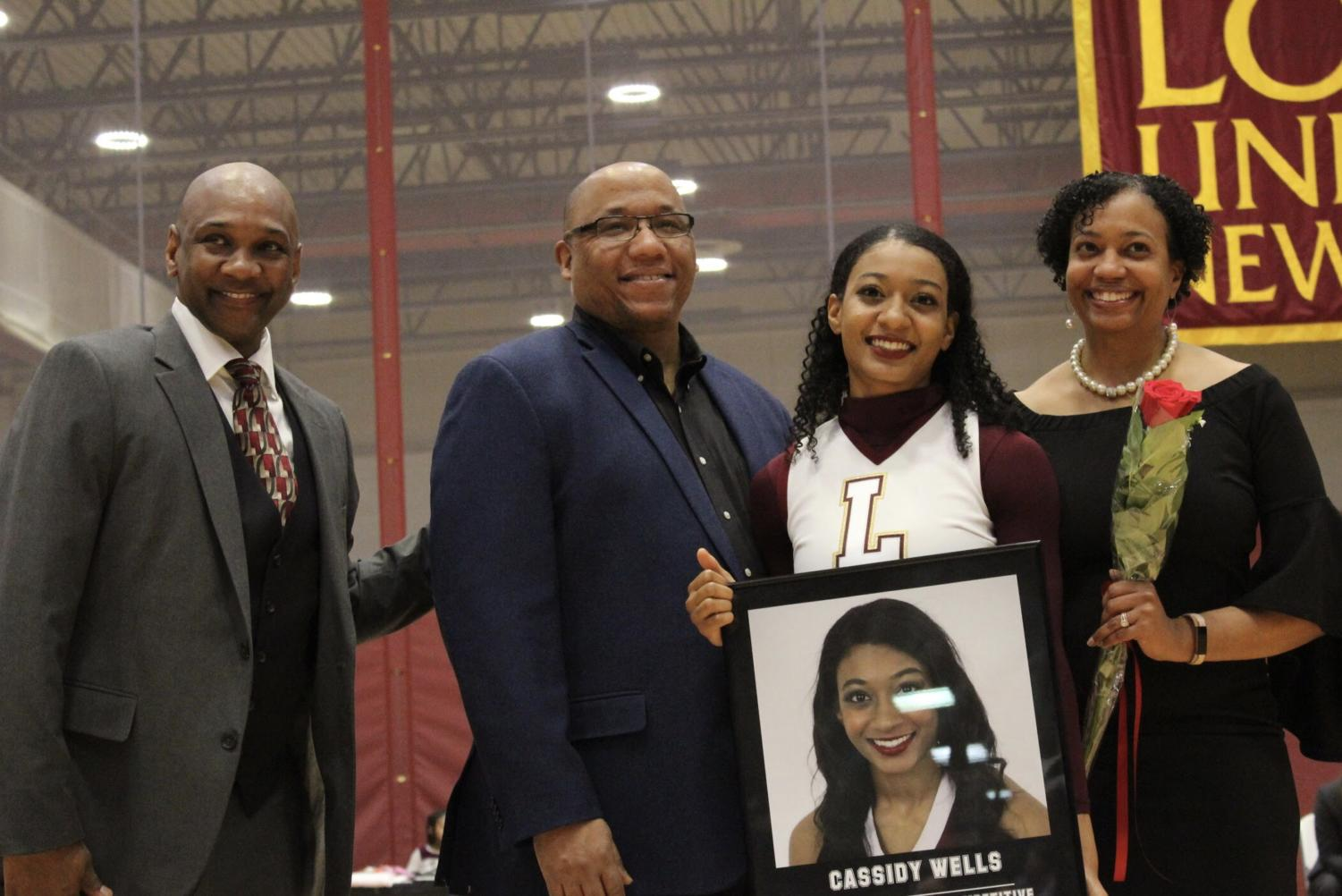 Criminal+justice+senior+Cassidy+Wells+poses+for+a+photo+with+her+family+and+cheer+head+coach+Rickey+Hill.+Photo+credit%3A+Rosha%27E+Gibson