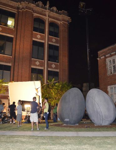 A film crew sets up and tests lighting for