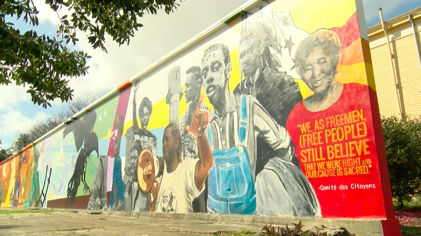 A mural commemorating U.S. civil rights struggles sits on display near the intersection of Royal Street and Homer Plessy Way. The mural, painted by artist Ayo Scott, was commissioned by the New Orleans Center for Creative Arts and presented to the public last year. Photo credit: India Yarborough