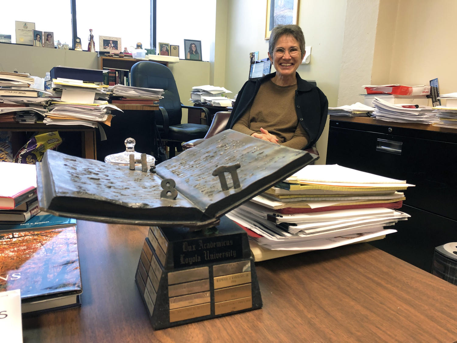 Isabel Medina, law professor, sits in her office surrounded by her work and the Dux Academicus award Feb. . The annual award recognizes a Loyola faculty member for their superior scholarship and teaching. Photo credit: Erin Snodgrass