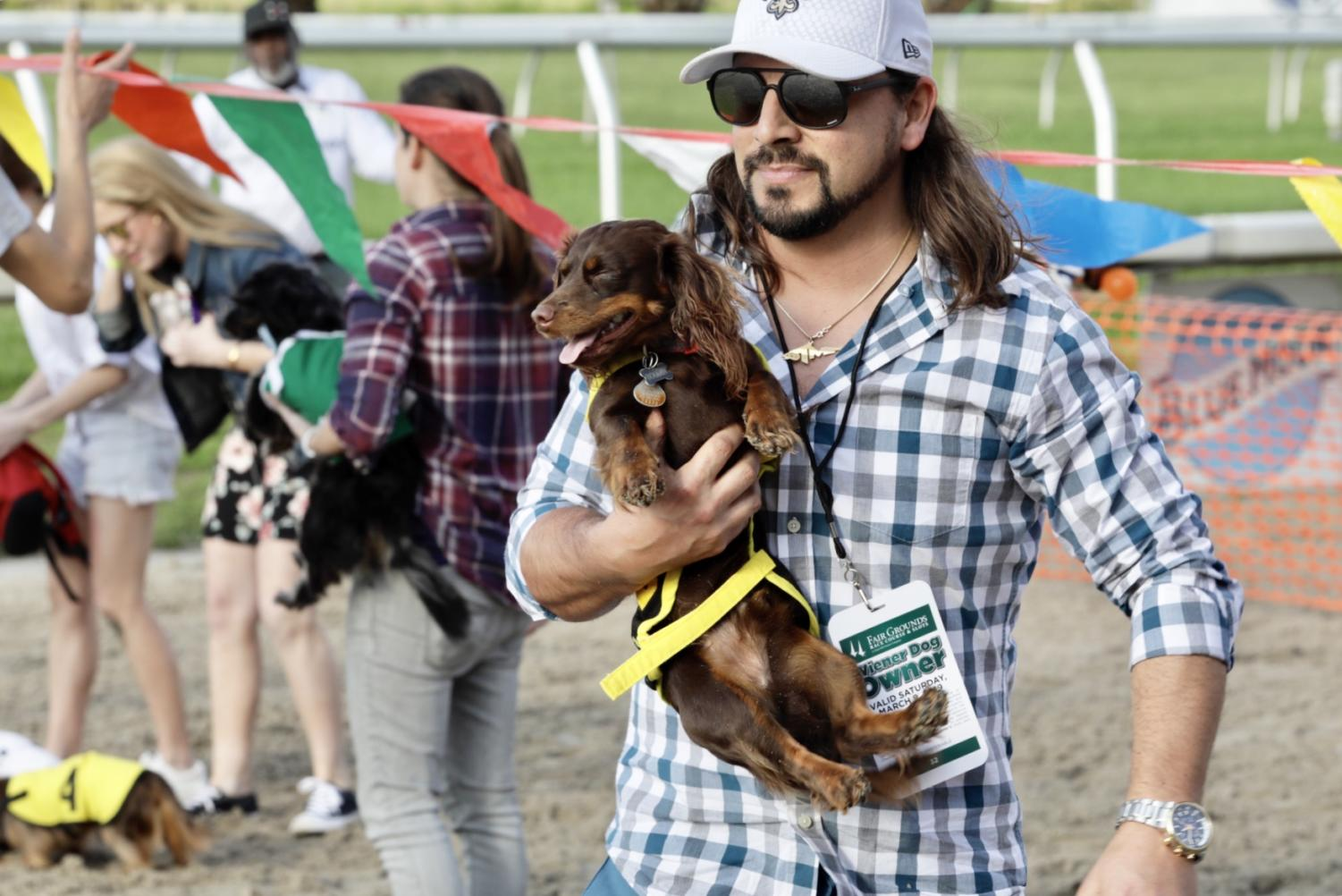 An+owner+picks+up+his+dog+after+a+race.+Some+dogs+underwent+diets+and+intensive+fetch+exercises+to+train+for+the+race.