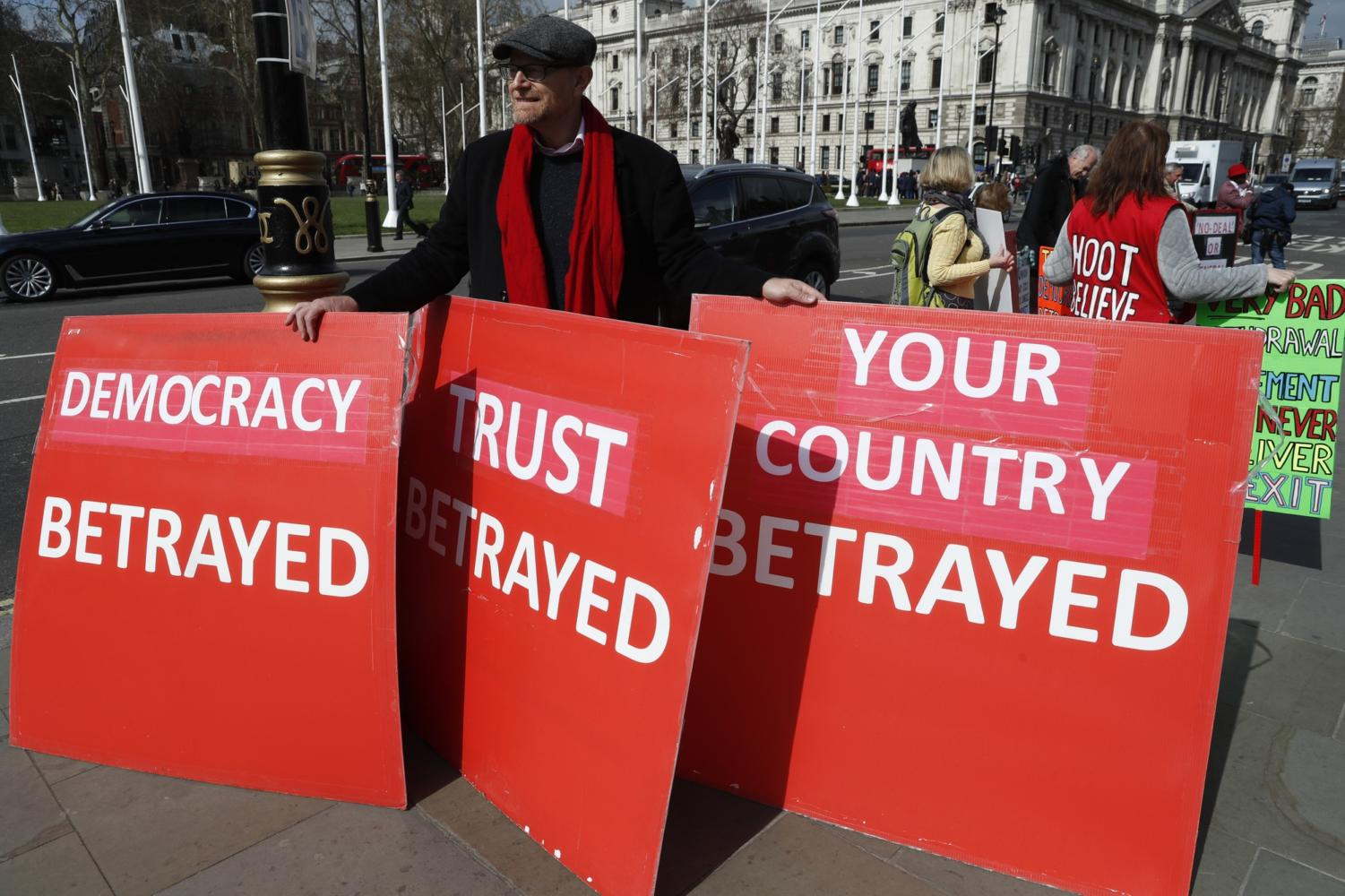 A pro-Brexit protester holds onto placards as he demonstrates near the House of Parliament in London, Tuesday, March 26, 2019. British Prime Minister Theresa May's government says Parliament's decision to take control of the stalled process of leaving the European Union underscores the need for lawmakers to approve her twice-defeated deal. (AP Photo/Alastair Grant)