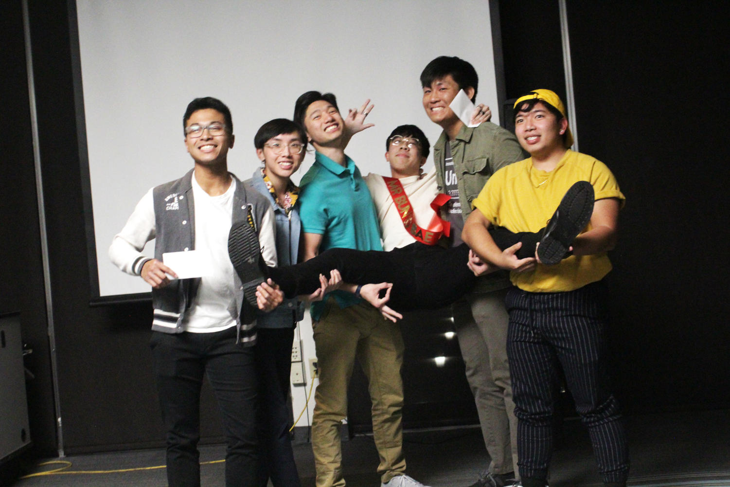 "Fellow contestants David Huynh, Brandon Nguyen, Thomas ""Titan"" Nguyen, Peter Vu and Kiet Phung hold up the winner of Loyola's Asian Student Organization's Mr. Bun Bo Bae  pageant, Danny Vo on March 16, 2019. Photo credit: Shamaria Bell"