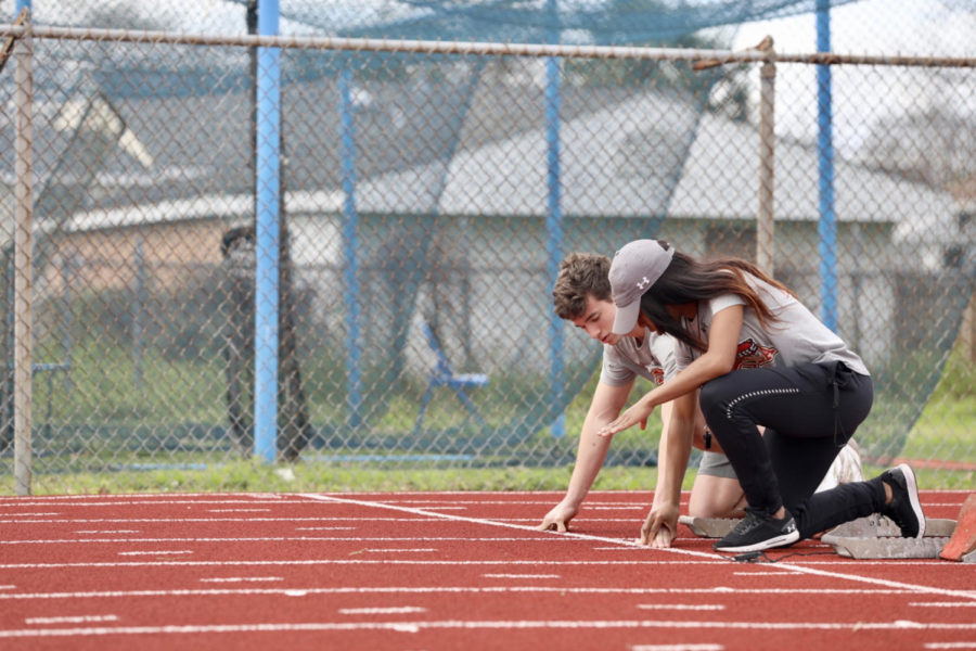 Track+and+field+assistant+coach+Amani+Bryant+helps+a+sprinter+with+his+exercises.+The+track+program+practices+at+East+Jefferson+High+School.+Photo+credit%3A+Andres+Fuentes