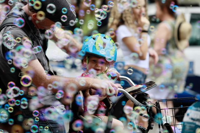 A+father+rides+with+his+daughter+in+a+bicycle+through+bubbles+on+Decatur+Street.+The+French+Quarter+Fest+prides+itself+on+its+family-friendly+atmosphere.