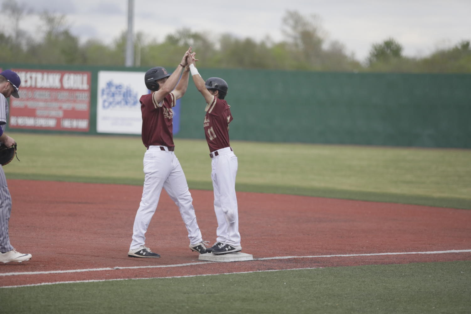 Two Loyola baseball players celebrate an offensive play at Segnette Field. The baseball team earned 12 conference awards. Photo credit: Andres Fuentes