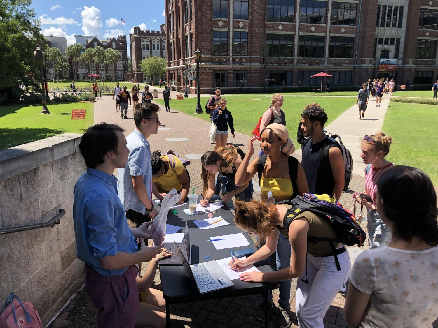 Students sign a petition advocating for condoms to be sold on campus on Sept. 3, 2019.